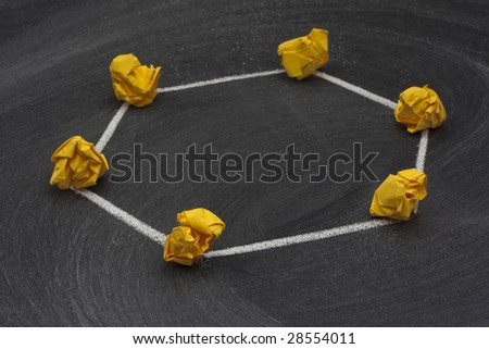 model of ring network with a single direction data flow made with yellow crumbled paper nodes, white chalk connection lines and blackboard with eraser smudges in background