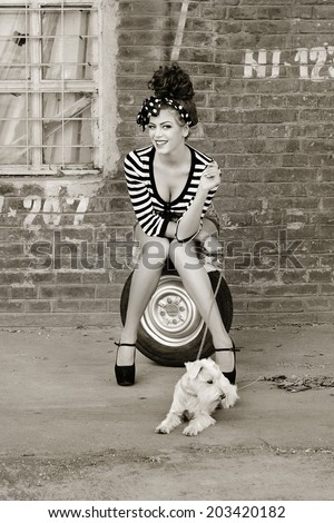 Model poses with dog. Edited in sepia - stock photo