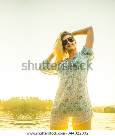 Model posing at  water texture. Sunset at beach. Woman wear transparent blue dress with flowers pattern and sunglasses against sunny sky and forest trees. Blond sexy girl  - stock photo