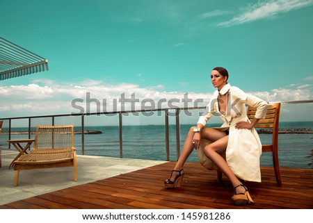 Model posing fashion in cream dress with accessories at seaside - stock photo