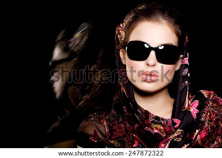 Model posing in sunglasses and embroidered shawl.
