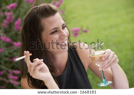 Model Release 351  Young woman relaxing with a glass of wine and a cigarette in an outdoor cafe - stock photo