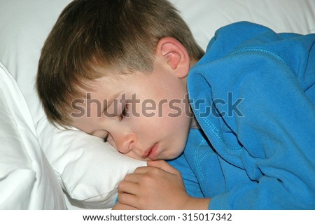 Model released image of Young preschool age boy sleeping on a white pillow wearing blue pajamas - stock photo