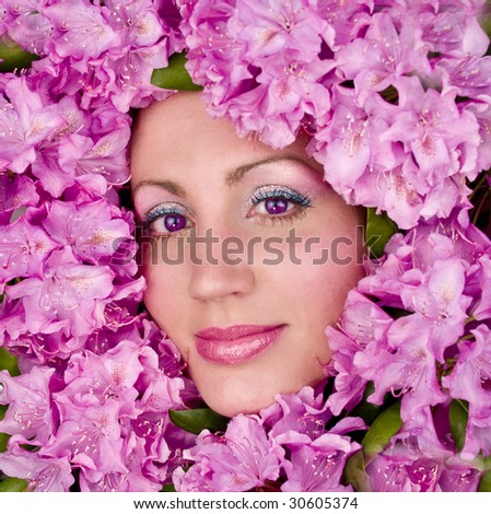 Model's face framed in rhododendron flowers with sparkly makeup