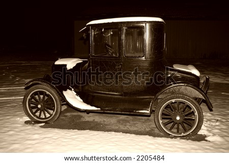 Model T car at night in the snow and sepia