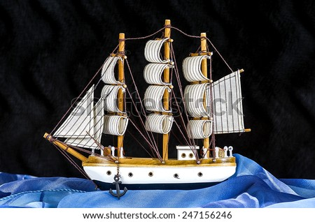 Model white sailboat with three masts on a black  - stock photo