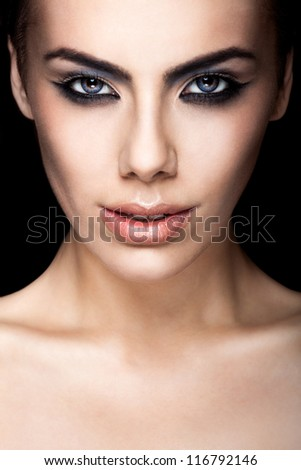 model with blue eyes looking at the camera on black background - stock photo