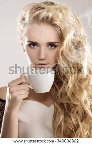 Model with coffee cup, mug in coffee shop. Fashion Woman, tea party time. Green Black. Blonde girl, tea set