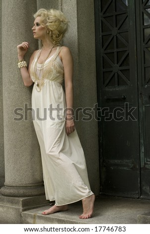 Model with cream dress and accessories poses with a tall hairstyle