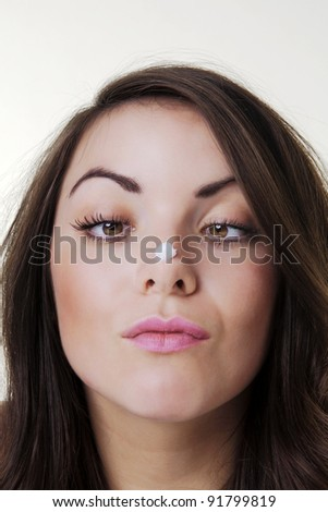 model with face cream on the end of her nose - stock photo