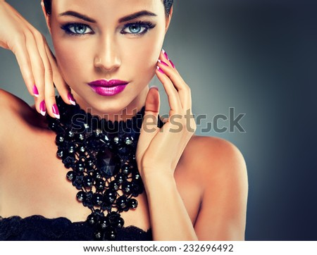 Model with fashionable nail Polish fuchsia and black necklace - stock photo