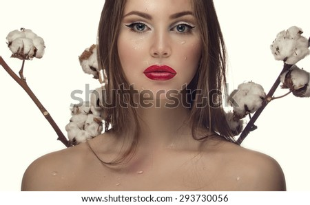 Model with water drops on the face and branches of cotton on a white background - stock photo