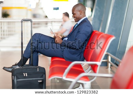 modern african businessman using tablet computer at airport - stock photo