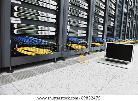 modern aluminium thin laptop computer at server network room representing concept of control and remote access and support - stock photo