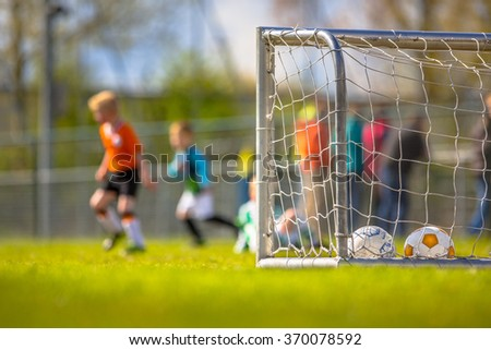 Modern aluminum soccer goal for youth with children training  in the background - stock photo