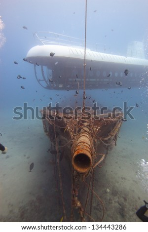 Modern and Ancient: A submarine hovers above an old ship wreck. - stock photo