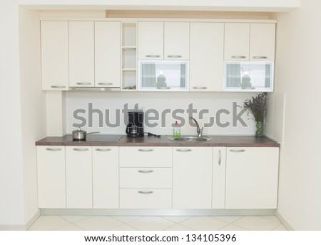 Modern and bright kitchen in house interior - stock photo