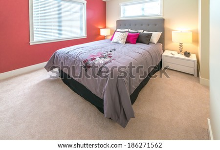 Modern and elegant luxury master bedroom with red color wall. Interior design. - stock photo