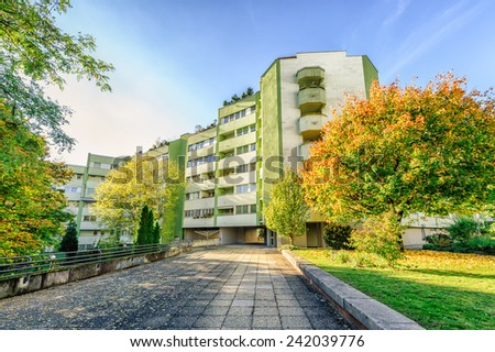 Modern apartment building with autumn colored trees - stock photo