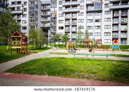 Modern apartment building with kids playground - stock photo