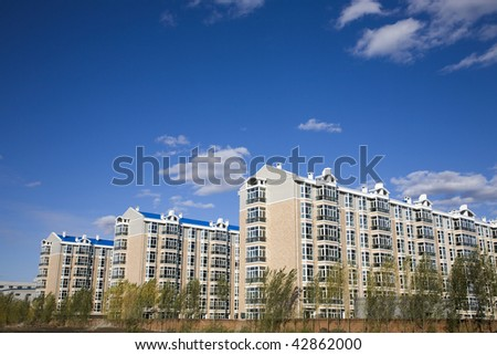 Modern apartment buildings under blue sky - stock photo