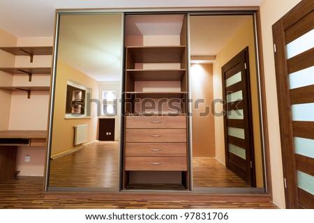 Modern apartment interior with huge wardrobe - stock photo
