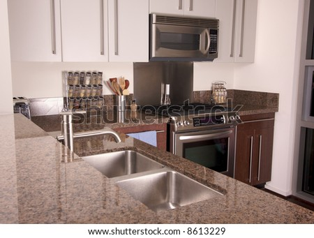 Modern Apartment Kitchen with brushed aluminum appliances. - stock photo