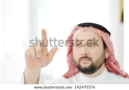 Modern arabic businessman with finger on copy space for your message - stock photo