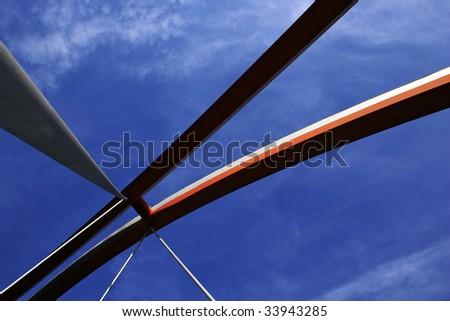 modern arch bridge against blue sky - stock photo
