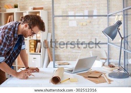 Modern architect looking at blueprint with sketch of construction in office - stock photo