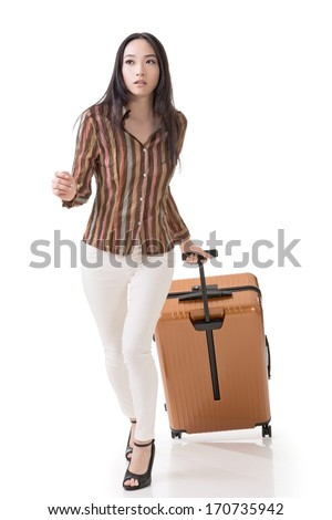 Modern Asian woman running and holding a suitcase, full length portrait isolated on white background.