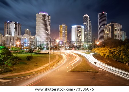 modern australian city at night with moving clouds in background and traffic car lights in foreground (broadbeach,gold coast,qld,australia)