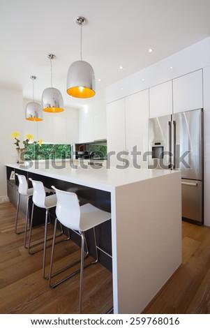 Modern Australian kitchen renovation with waterfall stone island bench - stock photo