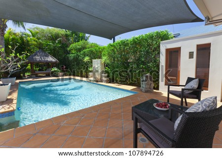 Modern backyard with swimming pool and Bali hut in Australian mansion - stock photo