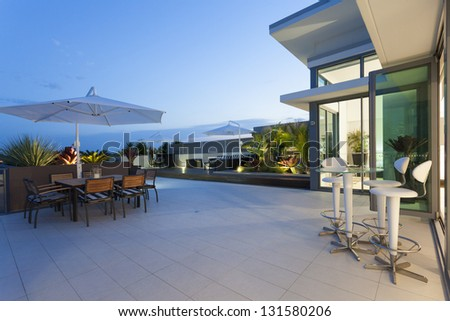 Modern balcony at sunset in luxury penthouse - stock photo