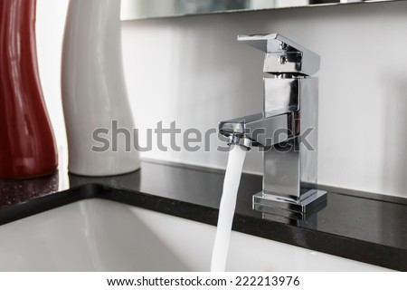 Modern bathroom faucet - stock photo