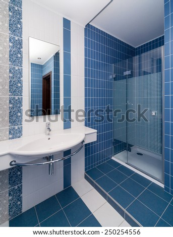 Modern bathroom tiled with white and blue tiles  - stock photo