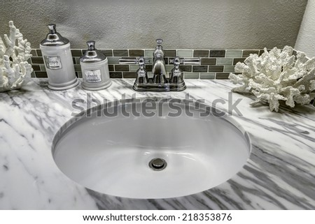 Modern bathroom vanity cabinet with white granite top. Sink view. White sink with steel faucet and decorated corals - stock photo