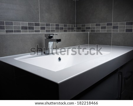 Modern bathroom washbasin with chrome faucet and gray tiling - stock photo