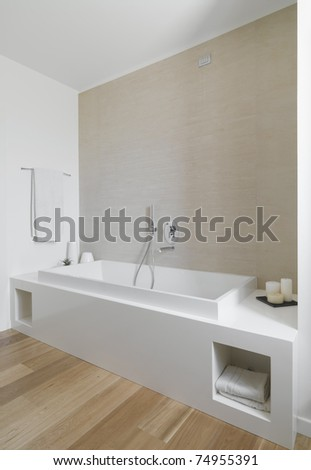 modern bathroom with a bathtub and wood floor - stock photo
