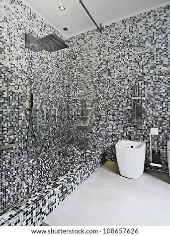 modern bathroom with bath and shower, the walls made of mosaic tile - stock photo