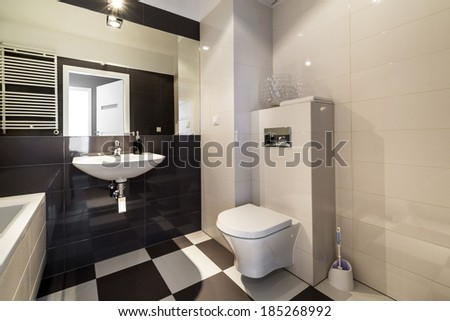 Modern bathroom with bathtub in beige color - stock photo