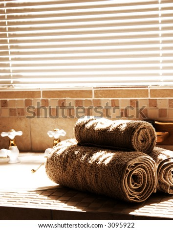 Modern bathroom with blinds on the window and rolled up towels. Shot in the morning, with bright sun coming through the blinds. - stock photo