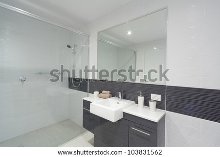 Modern bathroom with shower, sink and mirror. - stock photo