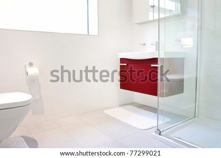 Modern bathroom with wall hung toilet and sink unit - stock photo