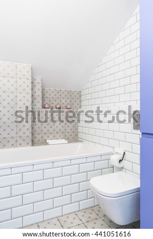 Modern bathroom with white brick effect tiles and toilet