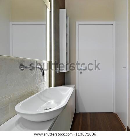 modern bathroom with white door and wood floor - stock photo
