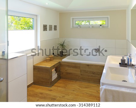 modern bathroom with wooden floor, bathtub, sink and windows - stock photo