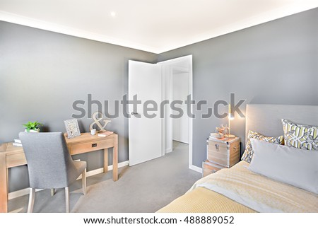 Modern bedroom and workroom at the same place and inside of a luxury house with wooden box lamp illumination beside the pillows, cushion, chair near to wooden table have a 3d letter next to door entry