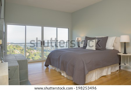 Modern bedroom composition with hardwood floor and mountain view. - stock photo